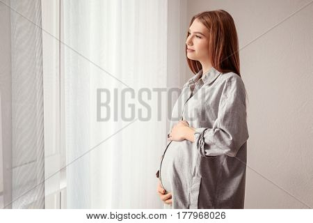 Beautiful pregnant woman standing near window at home