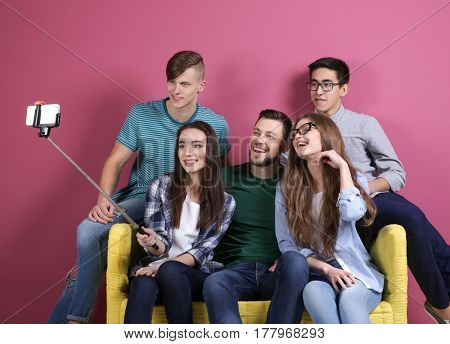 Young friends taking selfie while sitting on sofa against color background