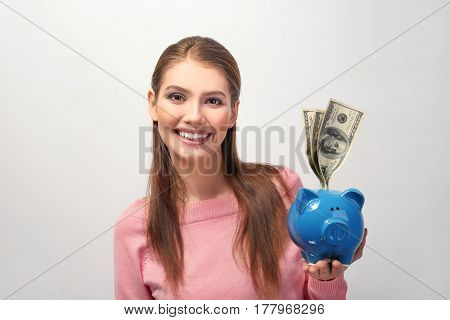 Beautiful young woman with piggy bank on light background