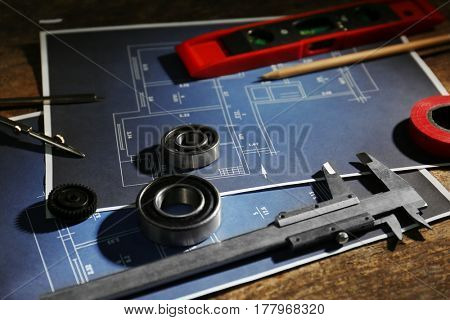 Different kinds of engineering tools and construction drawings on wooden background