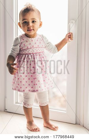 Cute Afro American baby girl is looking at camera while standing on the window sill at home
