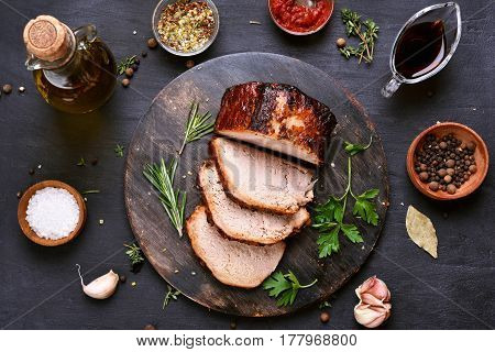 Sliced grilled pork barbecue meat on wooden cutting board over dark background top view