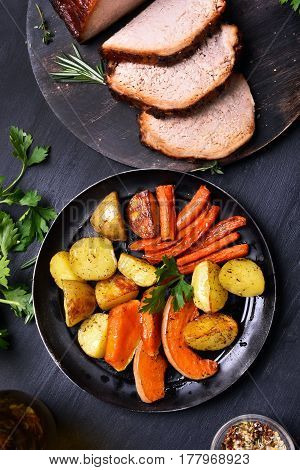 Roasted vegetables in frying pan and sliced meat top view. Focus on vegetables
