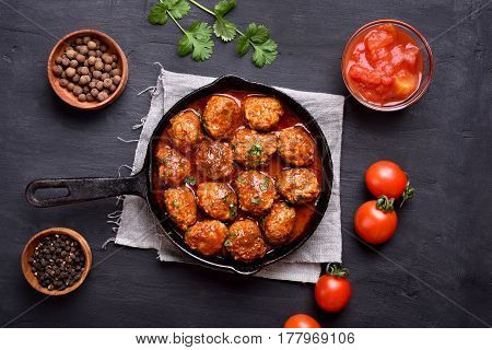 Meatballs with tomato sauce and green herbs in frying pan on dark background top view