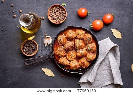 Meatballs with tomato sauce in frying pan on dark background top view