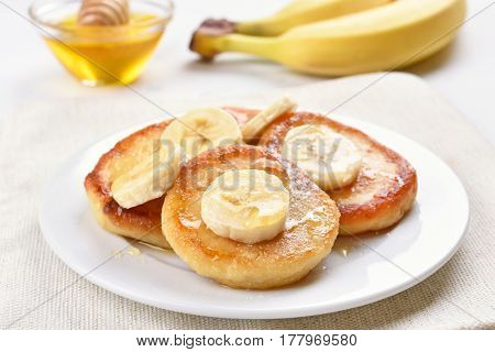 Pancakes with cottage cheese and banana slices healthy breakfast close up view