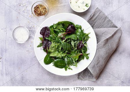 Spring salad with green leaves of spinach arugul on light stone background. Healthy food top view