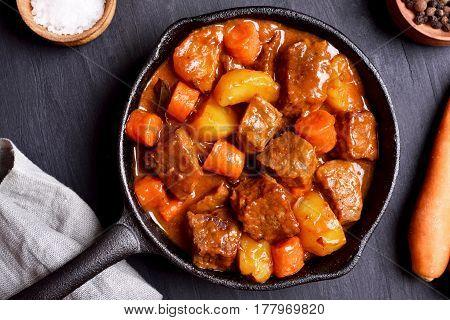 Beef stew in frying pan on dark background top view