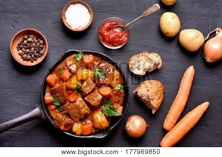 Goulash beef stew and ingredients on dark background top view