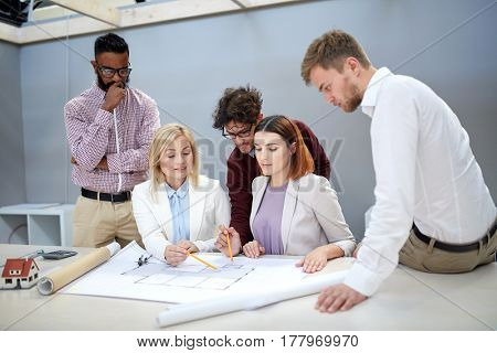 building, construction, architecture, real estate and people concept - business team with blueprint meeting and discussing house project at office
