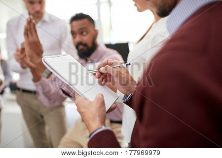 business, break, communication and people concept - happy creative team discussing something and man writing to notepad at office