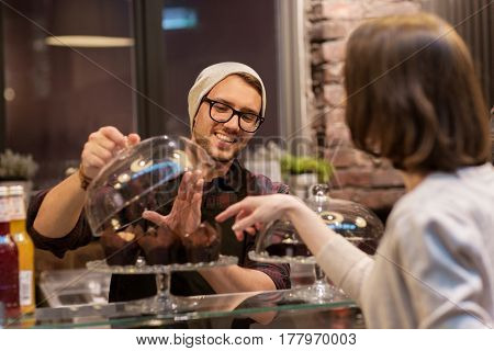 small business, food, people and service concept - happy man or barman with cakes serving female customer at vegan cafe