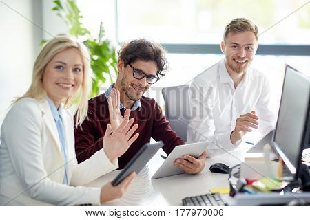 business, technology and people concept - creative team with tablet pc computers waving hands at office