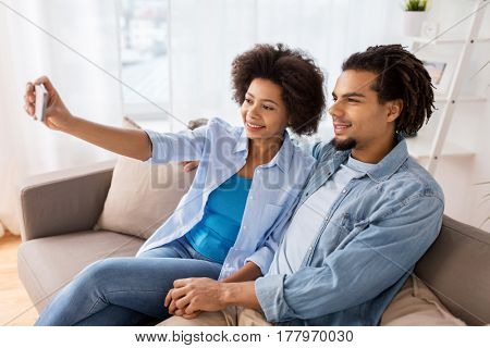 family, technology and people concept - happy couple with smartphone taking selfie at home