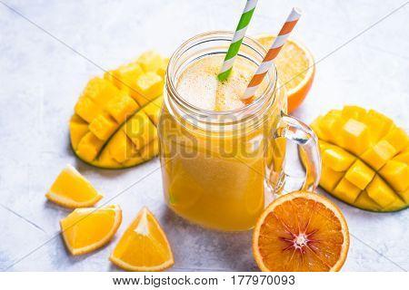 Mango orange juice smoothie grey concrete table. Fresh healthy drink.