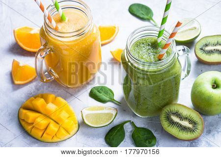 Green and yellow drink. Mango orange juice smoothie and kiwi apple spinach on grey concrete table. Fresh natural drink.