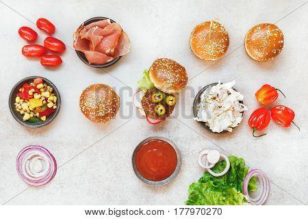 Preparing homemade burgers, various fillings on rustic surface. Top view, blank space