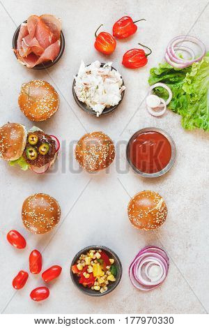 Mini party burgers with a dip and various fillings on rustic surface. Top view, blank space