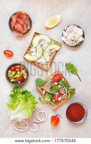 Two different open sandwiches from whole grain bread with ingredients on rustic surface. Top view, blank space