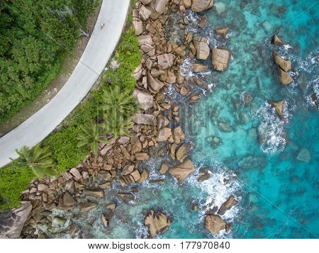 Seychelles La digue island aerial landscape of coastline and a road seascape. Top view of people cycling. Travel and transportation concept.