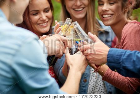 leisure, holidays, people, reunion and celebration concept - happy friends clinking glasses and celebrating at summer garden party