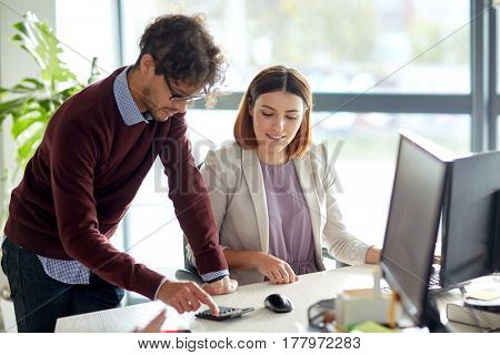 business, startup and people concept - happy creative team with calculator and papers in office