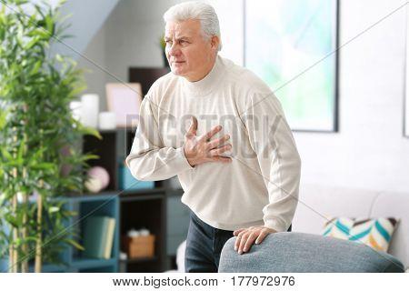 Aged man having heart pain, at home