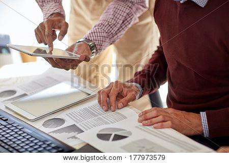 business, technology and people concept - businessmen with tablet pc computer and charts at office