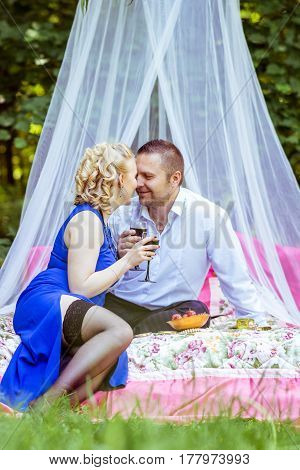 Man and woman sitting on the bed in the lawn and holding a glasses of wine and look at each other in Lviv, Ukraine.