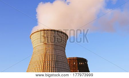 Water cooling tower stack smoke over blue sky background. Energy generation and air environment pollution industrial scene.