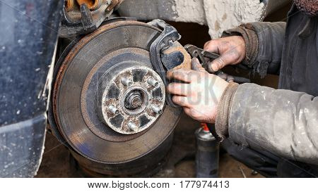 Auto mechanic working on brakes in a car repair shop domestic garage.