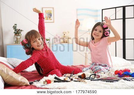 Cute little girls playing with their mother's stuff on bed