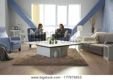 Two girls sitting on armchairs in beautiful living room