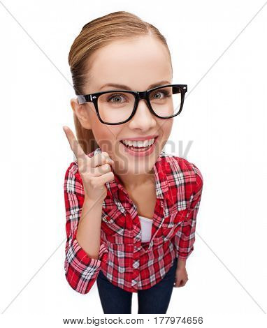 happiness and gesture concept - smiling teenager in eyeglasses with finger up, funny character with big head