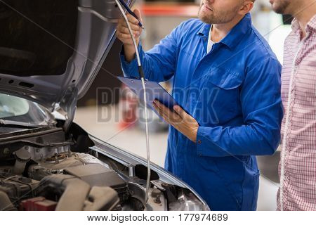 auto service, repair, maintenance and people concept - mechanic with clipboard and man or owner looking at broken car at shop