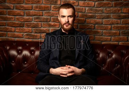 Imposing well dressed man sitting on a Chesterfield leather couch. Men's beauty, fashion.