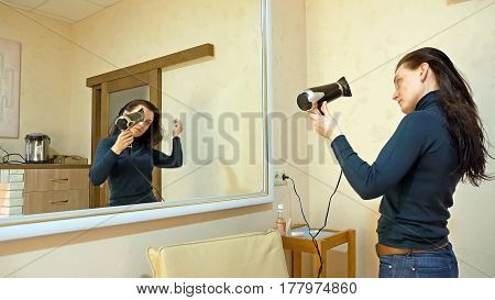 Beautiful brunette woman drying long black silky hair with hairdryer and smartens up in front of mirror in make-up dressing room.