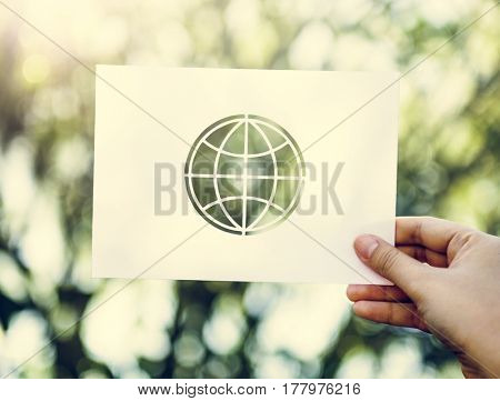Human hand holding globe perforated paper craft in nature