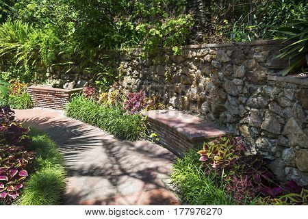 Walk path in garden decorated with stone to art bench.Intricate granite bench in a beautiful garden setting