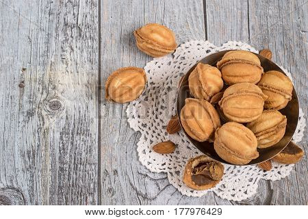 Homemade cookies in the form of a walnut, filled with sweet condensed milk and  almonds in a metal vase on a white openwork napkin.
