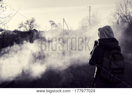 Village in smoke. Photographer takes picture of smoky road in evening sun. Rural landscape in spring. Toned black and white photo