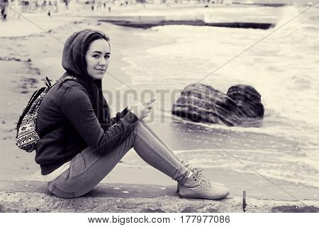 Girl on pier. Portrait of beautiful brunette in hood near stormy sea. Seascape with beach. Toned black and white photo
