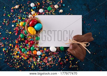 Delicious Chocolate Easter Eggs ,bunny Candy Sweets And White Card On Dark Blue Background