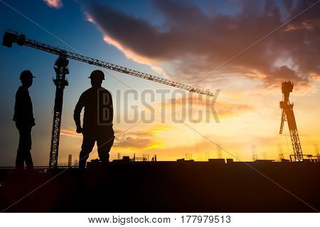 Silhouette engineer construction work control and blurred tower crane background on natural sunset sky.Heavy industry and building construction work concept.