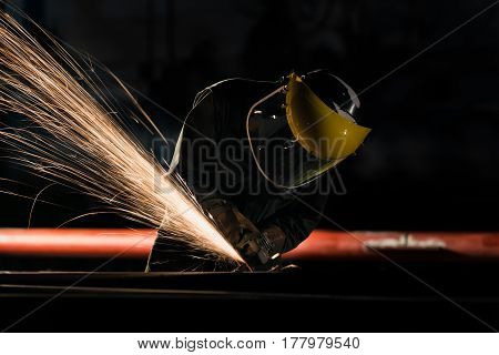 Worker with the face guard to electric wheel grinding on steel structure in factory