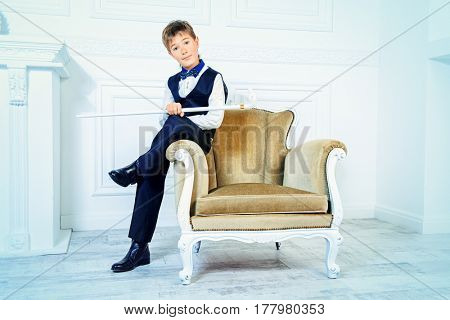 Handsome nine year old boy in elegant suit posing in luxurious apartments. Kid's fashion.