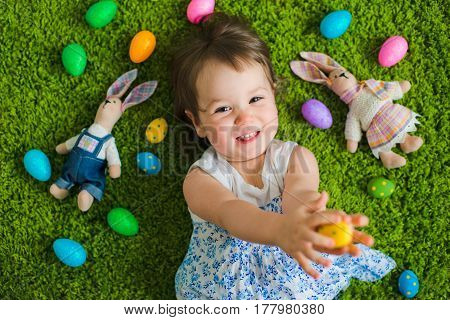 The child lies on the grass with Easter eggs and a hare