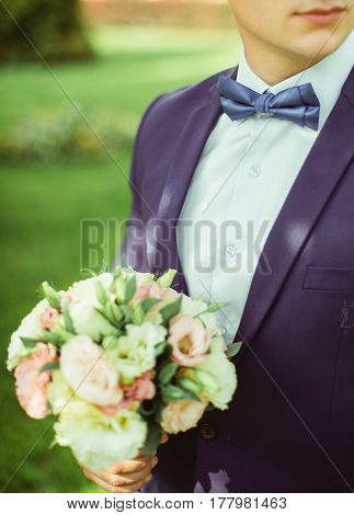 happy stylish elegant groom in a blue suit with a beautiful bouquet