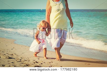 grandmother with little granddaughter walk at tropical beach