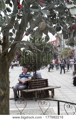 Decorative Sculptures. View To Crowded Street With Shops, Hotels, Transport And People In Bazaar Edi